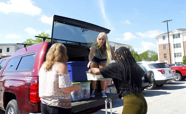 Katie Fyfe | The Journal Gazette  Charlet Kapke, left, and Antoinette Edwards, right, unload the car for move in day at Purdue Fort Wayne Student Housing on Wednesday.