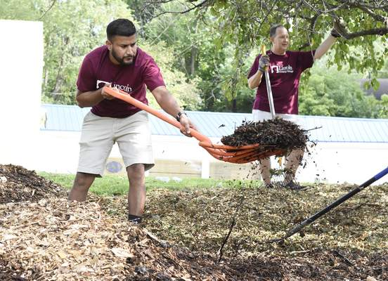 Rachel Von Stroup | The Journal Gazette  Dedi Nepal with Lincoln Financial Group works on mulching an area in front of Pool, Patio & Spas Inc. on Illinois Road during United Way of Allen County's Annual Day of Caring on Thursday.