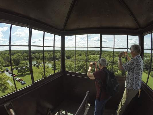 Mike Moore | The Journal Gazette Spectators take photos of surrounding Bluffton from the iconic Ouabache fire tower on Friday after its dedication and re-opening to the public.