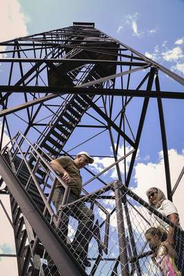 Photos by Mike Moore | The Journal Gazette People climb the Ouabache fire tower Friday to get a view of surrounding Bluffton not seen in years. The dedication ceremony came after donations from the Friends of the Ouabache State Park raised over $83,000 for the project.