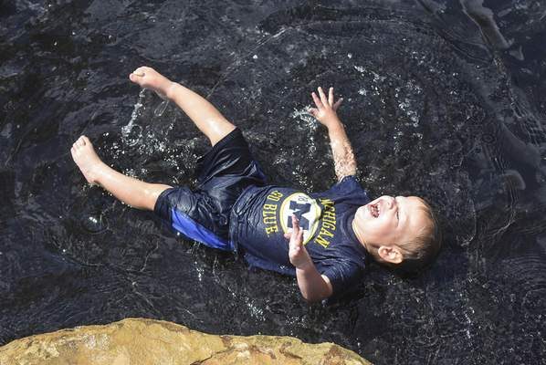 Michelle Davies | The Journal Gazette Griffin Good, 1, of Fort Wayne, takes a break in the Doermer Kids' Canal at Promenade Park Friday morning.