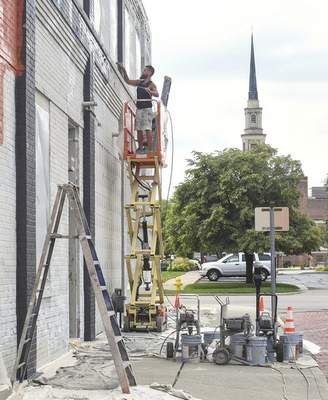 Michelle Davies | The Journal Gazette Russell Wishin, master painter with Ervin Brothers Painting, works on the facade of a building at the corner of Main and Webster Streets Thursday morning.