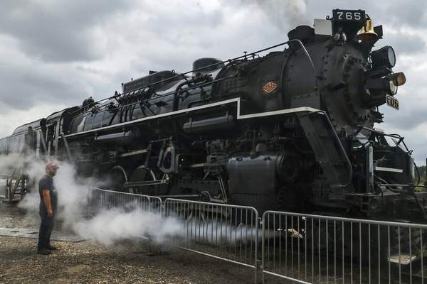 MIke Moore | The Journal Gazette  A spectator stands in clouds of steam let out by the historic Nickel Plate Road No. 765 during the Railroad Open House at the Fort Wayne Railroad Historical Society on Edgerton Road on Sunday.