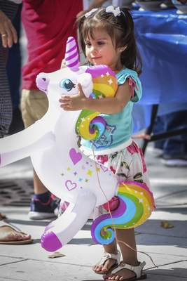 Mike Moore | The Journal Gazette  Isabella Martinez, 3, falls in love with her new inflatable unicorn bought by her mother while attending the Fiesta Fort Wayne event held at Headwaters Park on Saturday.