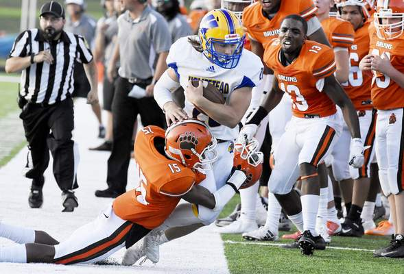 Rachel Von Stroup | The Journal Gazette Homestead's Braeden Hardwick keeps a hold of the ball as he is tackled by Northrop's Darrius Sanders into the sideline during the second quarter at Northrop on Friday night.
