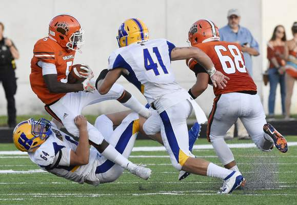 Rachel Von Stroup | The Journal Gazette Northrop's Jeremiah Green holds onto the ball as he is taken down by Homestead's Matt Miller during the second quarter at Northrop on Friday night.