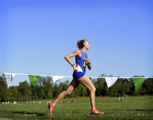 Katie Fyfe | The Journal Gazette  Homestead's Julia Dvorak runs with the letters WN painted on her arm in honor of West Noble's beloved cross country coach and teacher Chuck Schlemmer who passed away earlier this week.