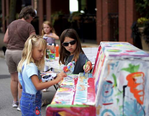 Katie Fyfe | The Journal Gazette  Elyse Schultz, 5, and Audrey Garlinger, 7, paint on a piano together during the 2019 Taste of the Arts Festival on Main Street on Saturday.