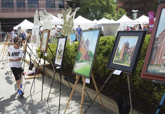 Photos by Katie Fyfe | The Journal Gazette Charlie Heath, 9, runs along a trail of paintings Saturday at the Taste of the Arts festival at Freimann Square.
