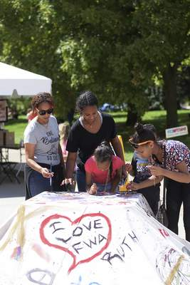 Katie Fyfe | The Journal Gazette The Sereke family adds their own artwork to the two-day downtown festival.