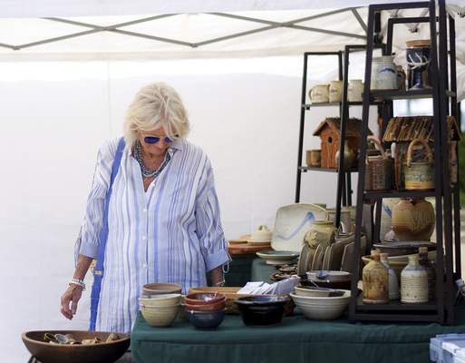 Katie Fyfe | The Journal Gazette  Mollie Royer looks at some pottery in one of the booths during the Taste of the Arts festival on Saturday.