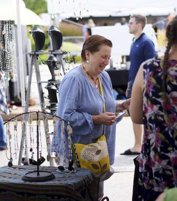 Katie Fyfe | The Journal Gazette  Sheila O'Roupke buys a necklace from one of the booths at the Taste of the Arts Festival on Saturday.