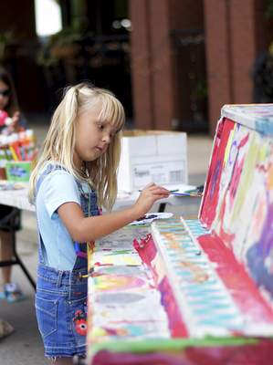 Katie Fyfe | The Journal Gazette Elyse Schultz, 5, paints a piano Saturday during the 2019 Taste of the Arts Festival on Main Street.