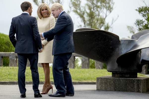 Associated Press U.K. Prime Minister Boris Johnson, right, meets French President Emmanuel Macron and his wife, Brigitte, at the G-7 summit Saturday.