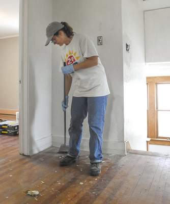 Michelle Davies | The Journal Gazette Gayle Goodrich sweeps the upstairs landing of the home she is renovating on Terrace Road.