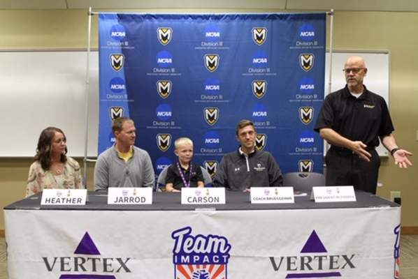 Courtesy  Six-year-old Carson McKee, who has cystic fibrosis, signs a letter of intent to join the Manchester University men's soccer team through nonprofit Team IMPACT's Draft Day celebration as, from left, his parents Heather and Jarrod McKee, head coach Corey Brueggeman and PresidentDave McFaddenlook on.