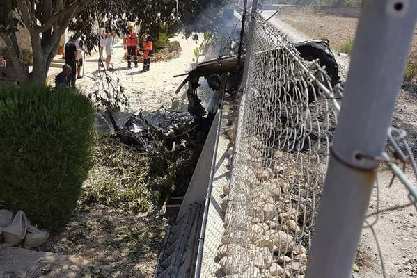 This photo provided by Incendios f.Baleares shows wreckage by a fence near Inca in Palma de Mallorca, Spain, Sunday Aug. 25, 2019. (Incendios f.Baleares Via AP)