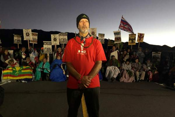 FILE - In this Monday, July 15, 2019, file photo, Dexter Kaiama, foreground, joins demonstrators gathered to block a road at the base of Mauna Kea, Hawaii's tallest mountain. (AP Photo/Caleb Jones, File)