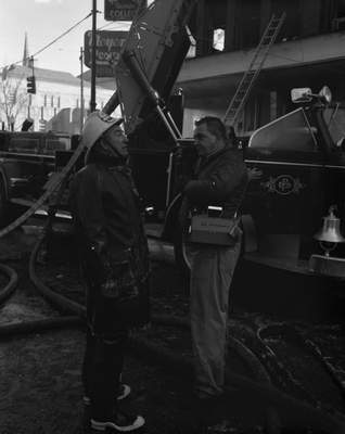 With his jacket fringed with frost and ice, Fort Wayne Assistant Fire Chief Main Graft, left, speaks with signalman Harold Norton, who is seen using one of the department's brand-new walkie-talkie units.