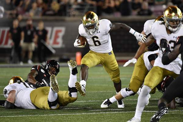 Associated Press  Notre Dame running back Tony Jones Jr. (6) runs through an opening in the Louisville defensive line during the first half Monday.