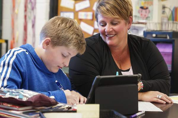 Mike Moore | The Journal Gazette  Jody Moher, a fifth-grade teacher at Leo Elementary School, sits with a student in her classroom last April.