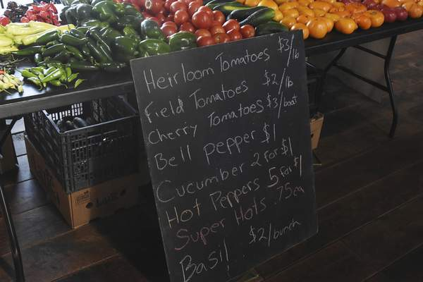 A board shows the prices of produce available by a vendor at the Salomon Farm Park Farmers Market. A new Purdue University study shows that prices of produce at farmers markets are comparable with, if not sometimes lower than, those of grocery stores.