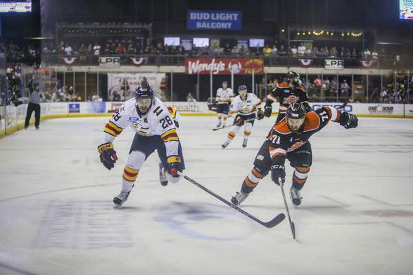 Tony Villalobos-May | Colorado Eagles  Shawn St-Amant, left, and the Komets' Ryan Lowney chase the puck during Game 7 of the Western Conference finals at the Budweiser Events Center in Loveland, Colorado, in 2018.