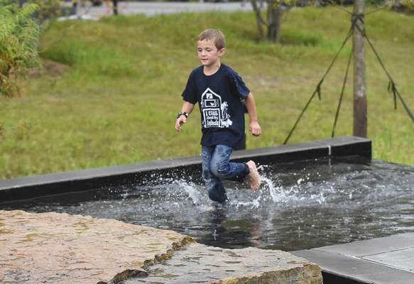 Michelle Davies | The Journal Gazette Making the most of his day in Fort Wayne, Connor Manz, 6, from Ohio, burns off his lunch at Coney Island by running through the fountain at Promenade Park on Tuesday.