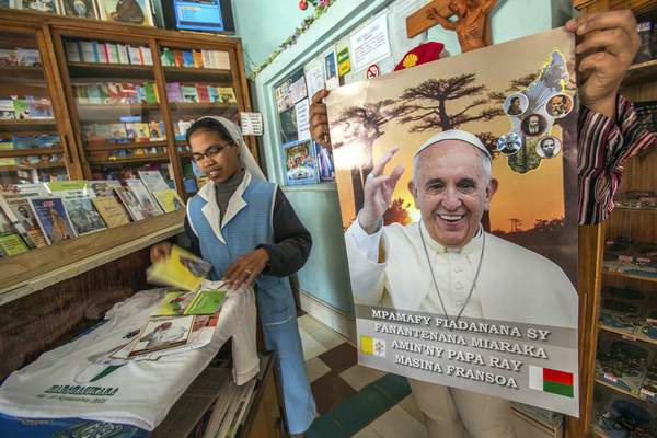 A nun browses in a store with Pope paraphernalia in Antananarivo, Madagascar, Tuesday, Sept. 3, 2019. (AP Photo/Alexander Joe)