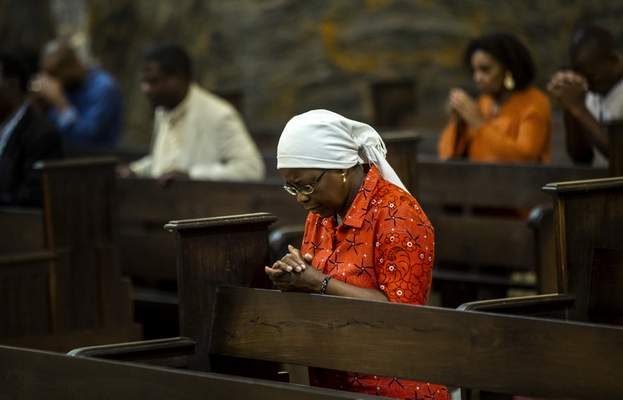 A woman prays during an early evening mass at the cathedral, which Pope Francis will visit later this week, in the capital Maputo, Mozambique Tuesday, Sept. 3, 2019. (AP Photo/Ben Curtis)
