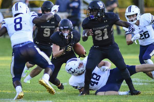 Mike Moore | The Journal Gazette Manchester University wide receiver Darren Lathrop carries the ball in the first quarter against Trine University at Burt Field on Thursday.