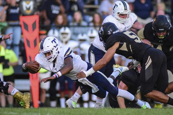 Mike Moore | The Journal Gazette Trine University quarterback Brandon Winters advances the ball for a first down in the second quarter against Manchester University at Burt Field on Thursday.
