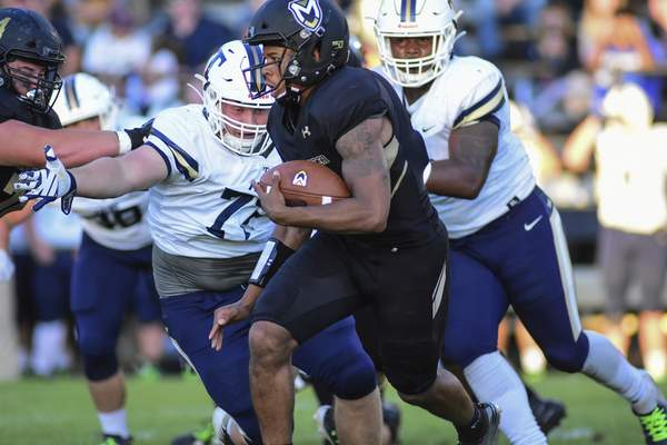 Mike Moore | The Journal Gazette Manchester University defensive back Jaquan Walker carries the ball in the first quarter against Trine University at Burt Field on Thursday.