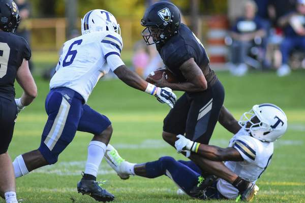 Mike Moore | The Journal Gazette Manchester University defensive back Jaquan Walker, center is brought down by Trine University inside linebacker Simeon Washington, right in the first quarter at Burt Field on Thursday.