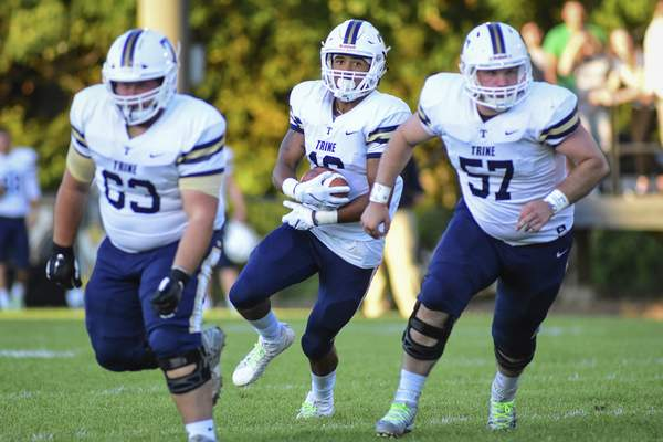 Mike Moore | The Journal Gazette Trine University tight end Dylan Dowling, center carries the ball with help from blockers Aaron Bergman, left and Tristan Edwards, right in the first quarter against Manchester University at Burt Field on Thursday.