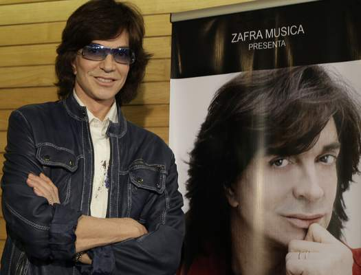 FILE - In this Nov. 4, 2009, file photo, Spanish singer Camilo Sesto poses next to a poster depicting himself during a news conference in Mexico City. (AP Photo/Gregory Bull, file)