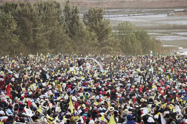 Pope Francis, background center, is cheered by a crowd of faithful as he arrives with the popemobile to celebrate a mass in Antananarivo, Madagascar, Sunday, Sept. 8, 2019. (AP Photo/Alessandra Tarantino)