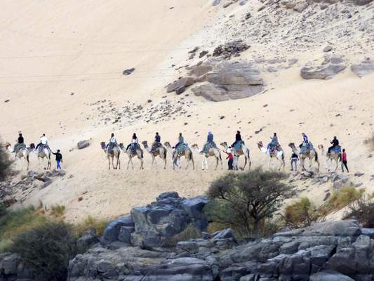 Courtesy Manchester University students ride camels on a visit to Egypt. An Egyptologist will speak at the college Tuesday.