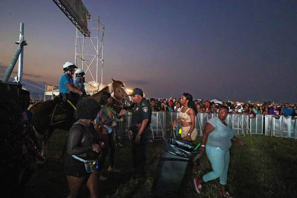 In this Saturday, Sept. 7, 2019 photo, Mounted New Orleans Police Department officers stand at the entrance during Lil Wayne's fifth annual Lil WeezyAna Fest at the UNO Lakefront Arena grounds in New Orleans. (Sophia Germer/The Advocate via AP)