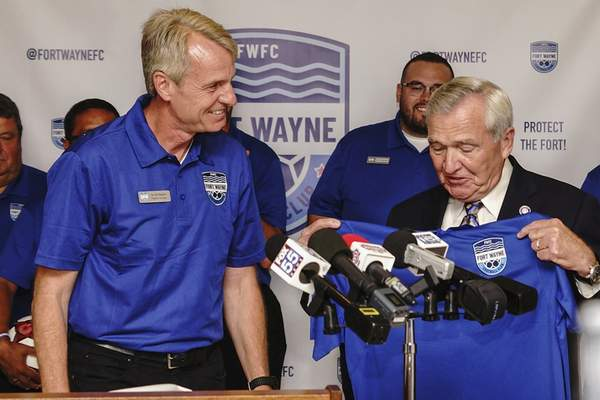 Fort Wayne Football Club president  Erik Magner presents a T-shirt to  Mayor Tom Henry at an announcement  of the new home of a National Premier Soccer League team. (Mike Moore | The Journal Gazette)