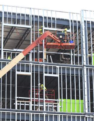 Michelle Davies | The Journal Gazette Crews work Tuesday inside and outside as the new Rescue Mission takes shape in downtown Fort Wayne at  Washington Boulevard and Lafayette Street.