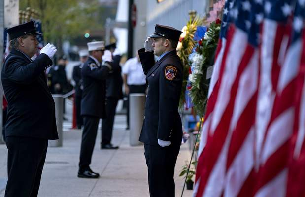 New York City firefighters salute in front of a memorial on the side of a firehouse adjacent to One World Trade Center and the 9/11 Memorial site during ceremonies on the 18th anniversary of 9/11 terrorist attacks in New York on Wednesday, Sept. 11, 2019. (AP Photo/Craig Ruttle)