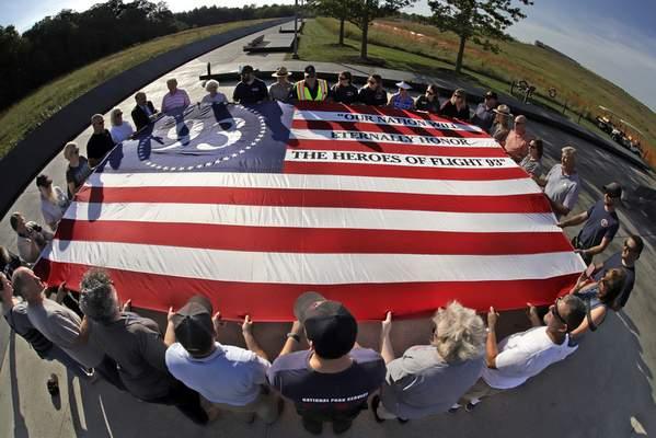 Visitors to the Flight 93 National Memorial in Shanksville, Pa., participate in a sunset memorial service on Tuesday, Sept. 10, 2019, as the nation prepares to mark the 18th anniversary of the Sept. 11, 2001 attacks. (AP Photo/Gene J. Puskar)