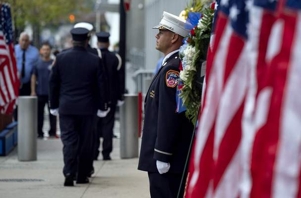 New York City firefighters take their positions in front of a memorial on the side of a firehouse adjacent to One World Trade Center and the 9/11 Memorial site during ceremonies commemorating the 18th anniversary of the 9/11 terrorist attacks in New York on Wednesday, Sept. 11, 2019. (AP Photo/Craig Ruttle)