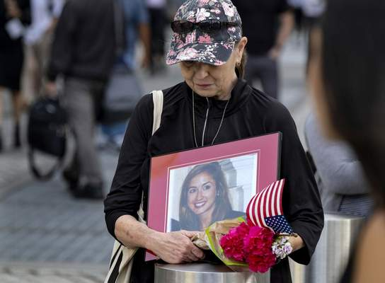 Connie Dray of West Virginia holds a photo Wednesday, Sept. 11, 2019, of her cousin Mary Lou Hague, who died in the World Trade Center attacks of Sept. 11, 2001, as she stands near One World Trade Center while ceremonies marking the 18th anniversary were underway nearby. This was Dray's first time at the ceremonies, saying it was on her list of important things to accomplish, as she also close with Hague's family. (AP Photo/Craig Ruttle)