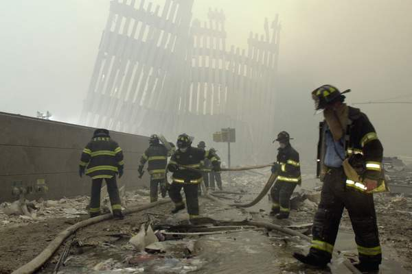 FILE - In this Sept. 11, 2001, file photo, firefighters work beneath the destroyed mullions, the vertical struts that once faced the outer walls of the World Trade Center towers, after a terrorist attack on the twin towers in New York. (AP Photo/Mark Lennihan, File)