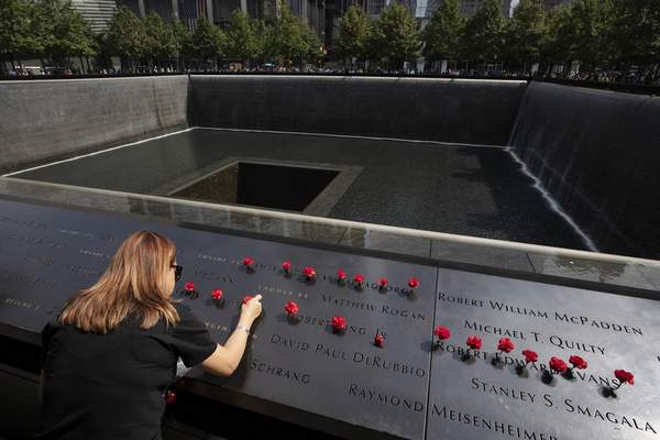 Norma Molina, of San Antonio, Texas, leaves flowers by the names of firefighters from Engine 33 at the September 11 Memorial, Monday, Sept. 9, 2019, in New York. (AP Photo/Mark Lennihan)