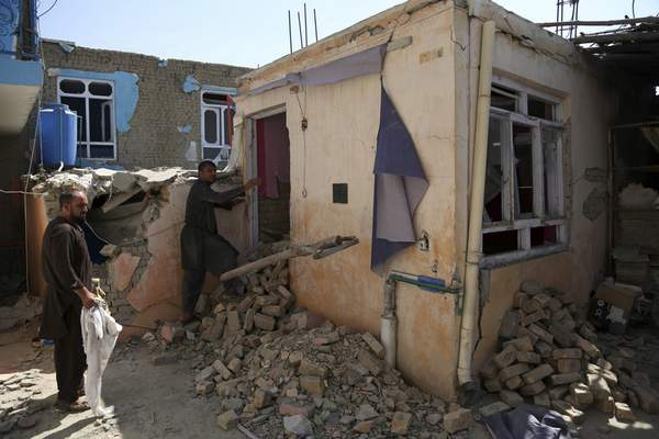 In this Tuesday, Sept. 10, 2019, photo, Afghans inspect their damaged house after a large explosion last week near a compound housing several foreign organizations and guesthouses, in Kabul, Afghanistan. (AP Photo/Rahmat Gul)