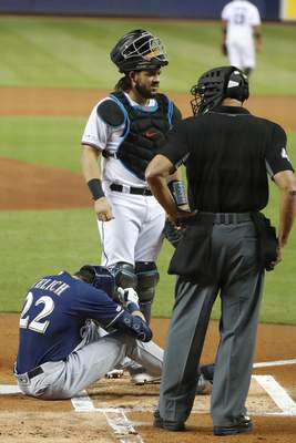 Associated Press Milwaukee Brewers' Christian Yelich sits on the ground after fouling a ball off of and shattering his kneecap on Tuesday.