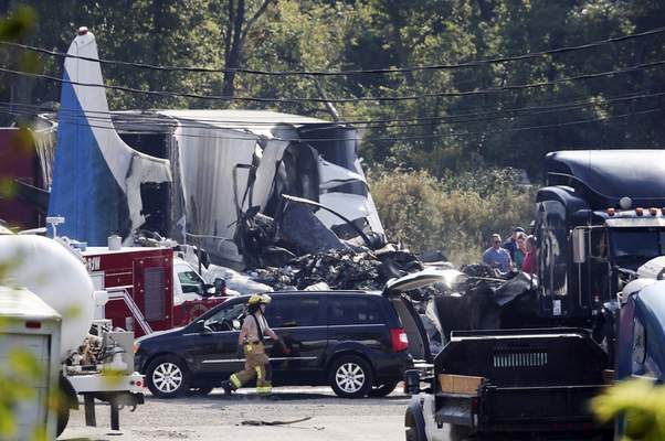 Smoke continue to rise from the wreckage after a small cargo plane crashed at an auto repair business near Toledo Express Airport Wednesday, Sept. 11, 20129, in Monclova, Ohio. (Dave Zapotosky/The Blade via AP)